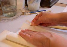 Découpe à la main, un par un, des onglets de réparation des fonds de cahier